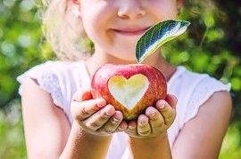 Girl holding apple with heart cut out